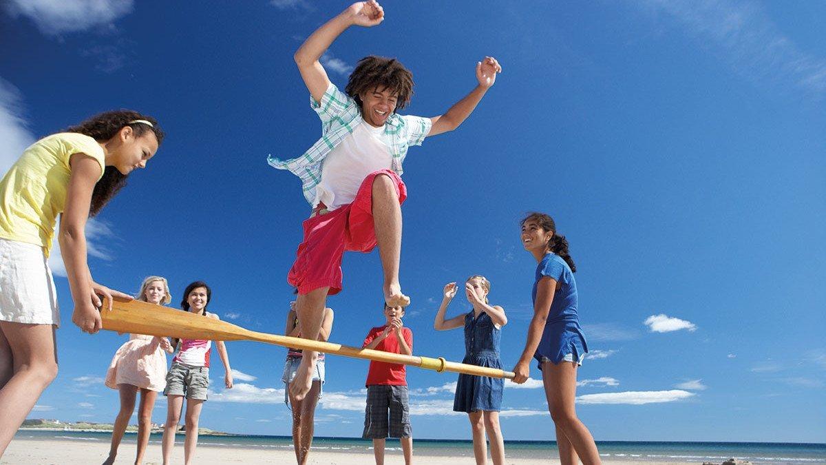 Junge springt über ein Paddel, welches von zwei Mädchen hochgehalten wird