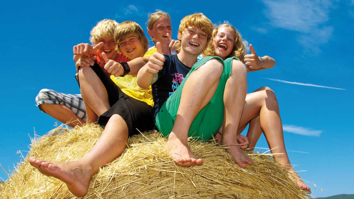 Schüler halten ihre Daumen hoch und sitzen auf einem Heuballen im Osnabrücker Land