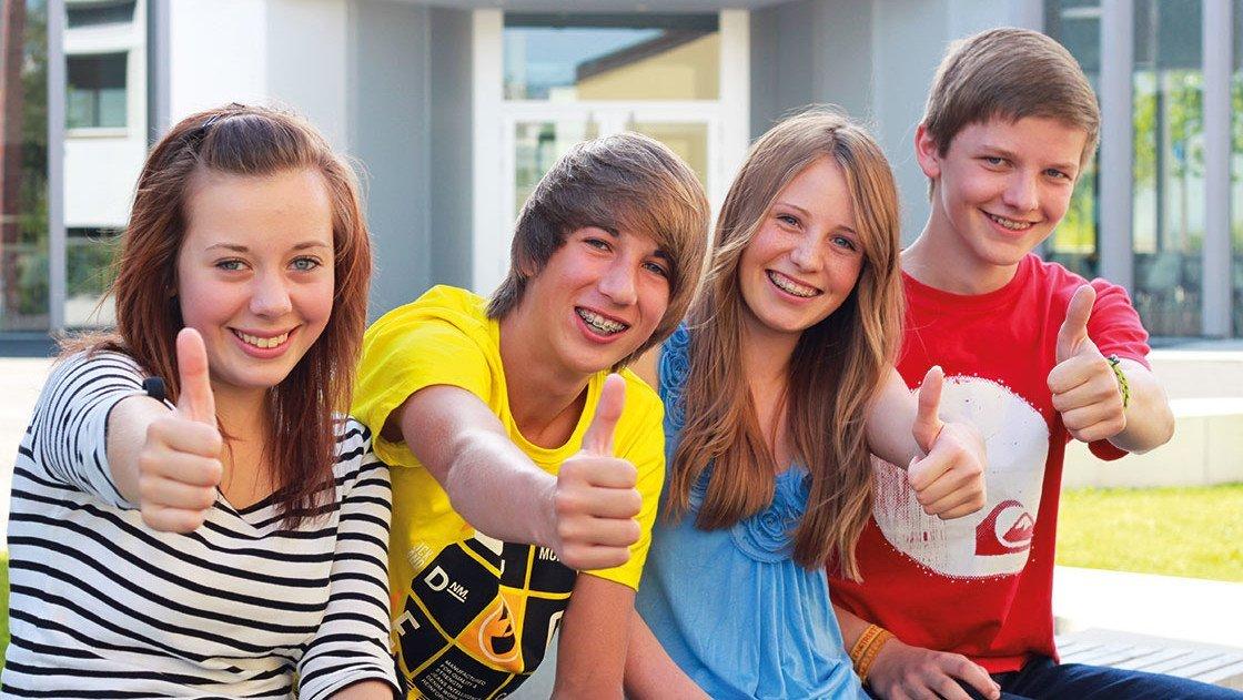 Junge Leute zeigen den Daumen hoch