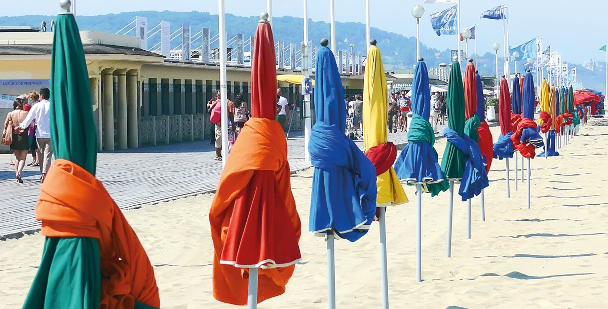 Bildschöne bunte Sonnenschirme am Strand in der Normandie