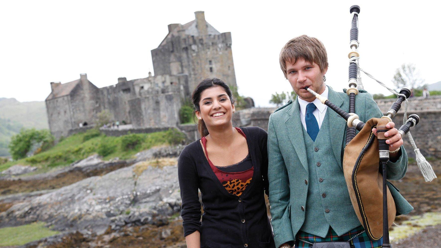 Schülerin mit Dudelsackspieler vor Burg