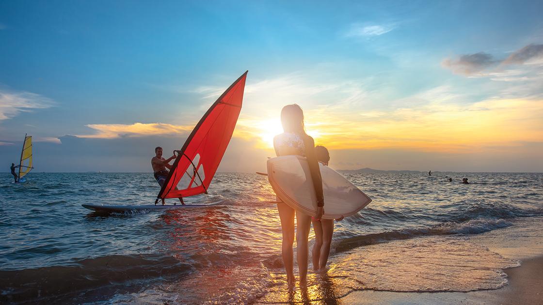 Schüler surfen an der Adriaküste bei Sonnenuntergang