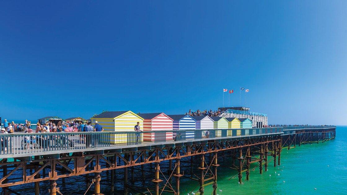 Blick auf den Pier in Hastings mit bunten Strandkabinen