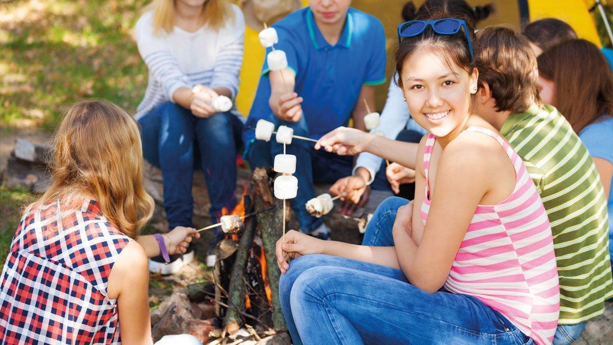 Schüler halten Marshmallows über dem Feuer