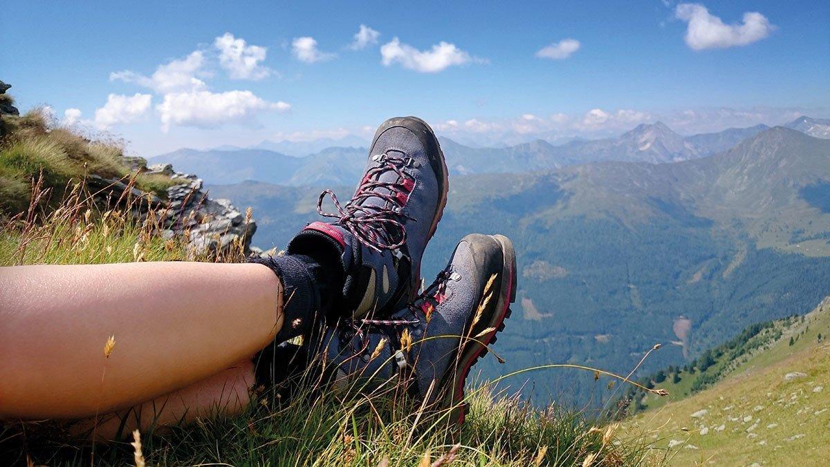 Eine Person ruht sich auf den Bergen aus und legt die Füße hoch
