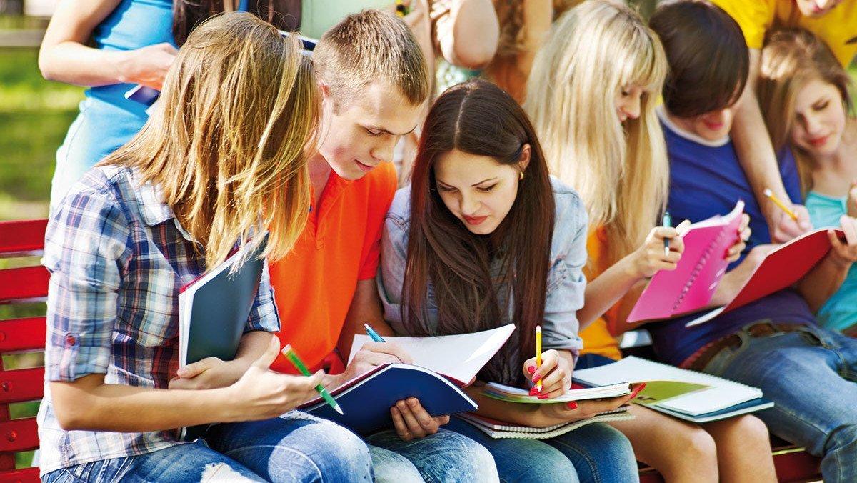 Schüler auf der Bank mit Büchern in der Hand