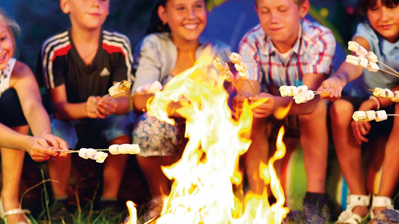 Junde Leute beim Lagerfeuer während einer Klassenfahrt am Edersee