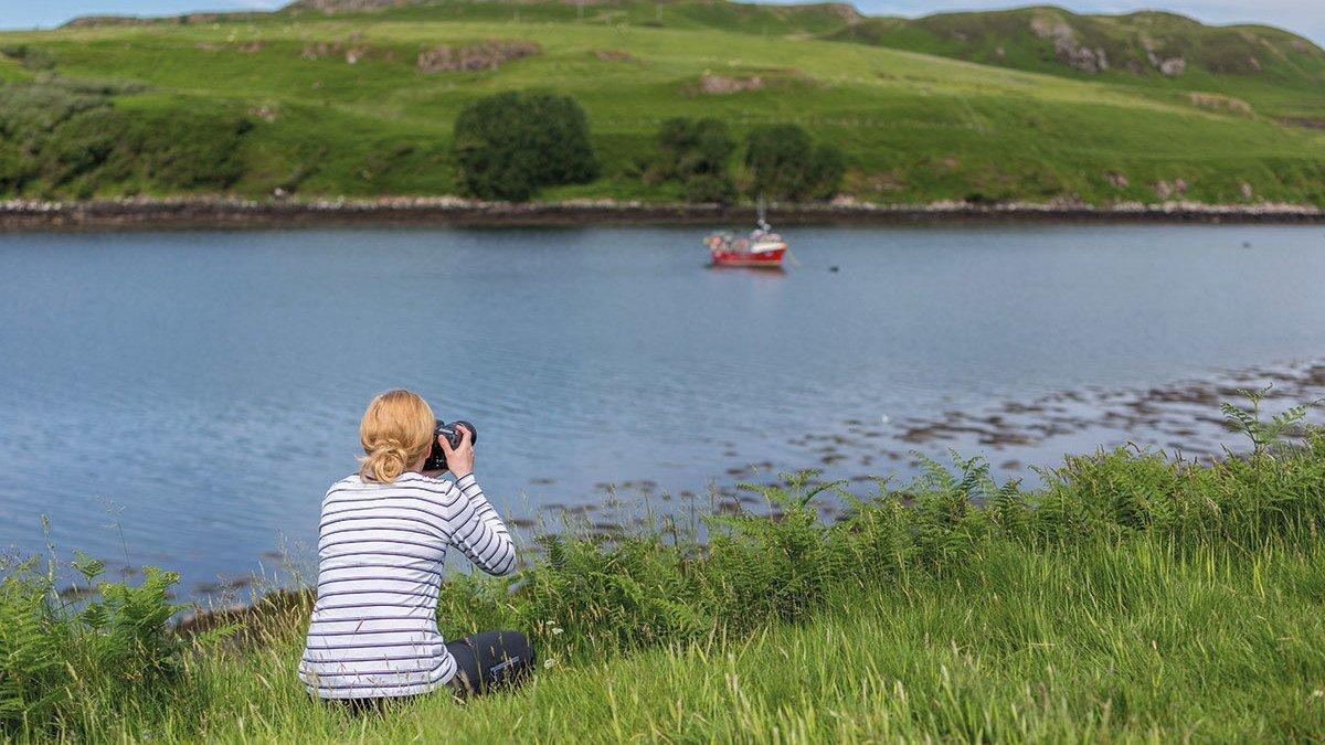 Junge Frau sitzt am Ufer eines Flusses und fotografiert