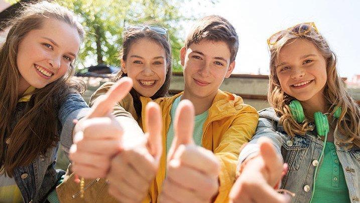 Gruppe junger Leute strecken den Daumen in die Luft