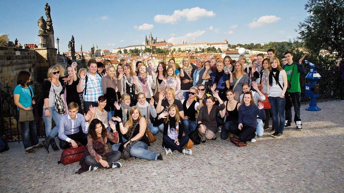 Schüllerklasse die sich vor der Kulisse von Prag fotografieren lässt