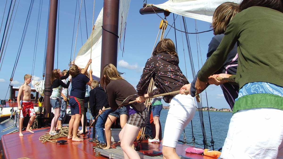 Schüler ziehen an den Leinen von einem Segelschiff auf dem Ijsselmeer