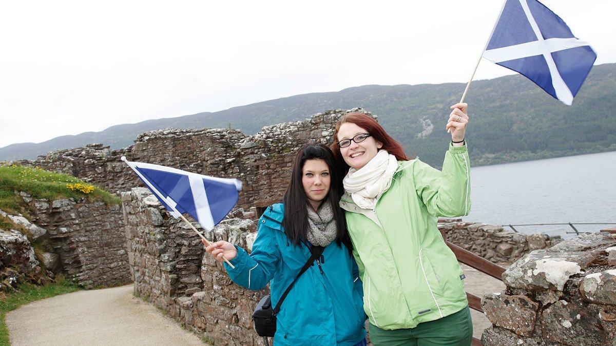 Jugendliche in Urquhart Castle in Schottland wähen eine Flagge im Wind