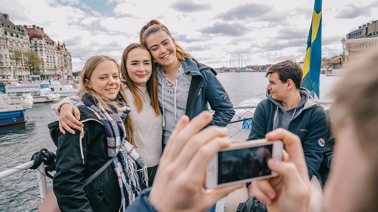Jugendlich machen ein Foto auf einem Boot