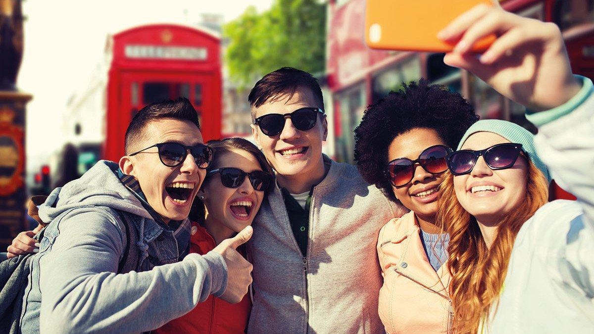 Jugendliche fotografieren sich vor einer alten Londoner Telefonzelle