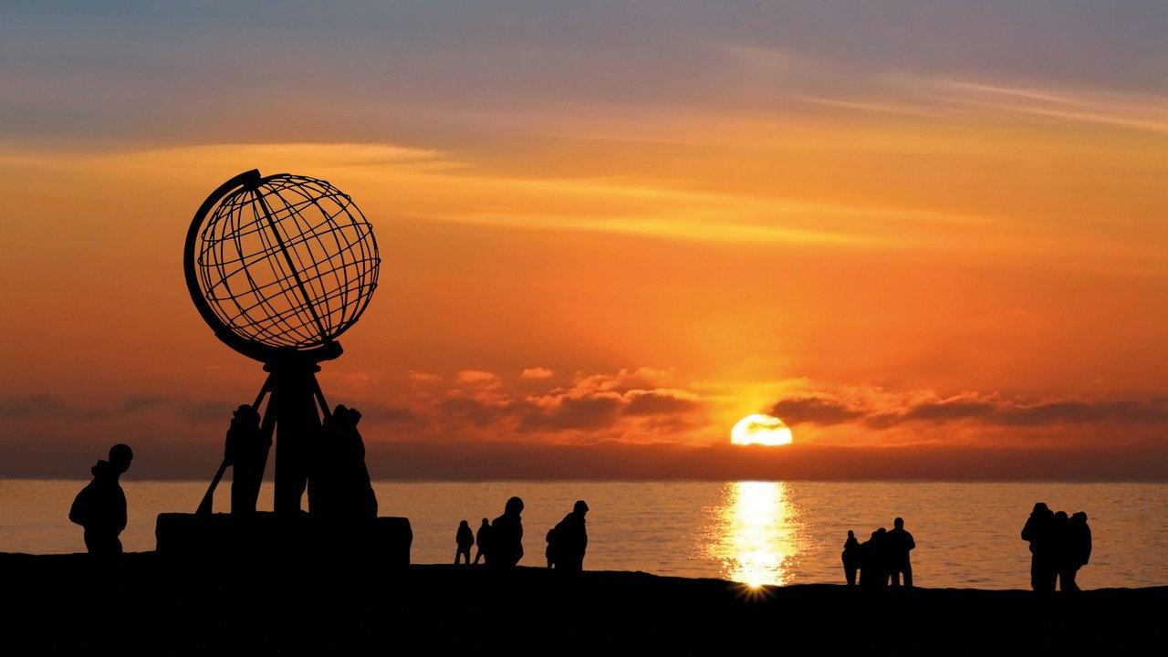 Eine Gruppe von Menschen am Nordkap bei Sonnenuntergang