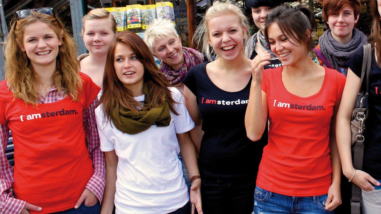 Eine Gruppe Schülerinnen mit ihrer Lehrerin auf Klassenfahrt in Amsterdam. Alle lachen und tragen rote und schwarze Shirts mit der Aufschrift I amsterdam. Amsteer