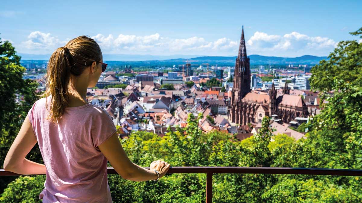 Schülerin auf einem Aussichtpunkt schaut über Freiburg
