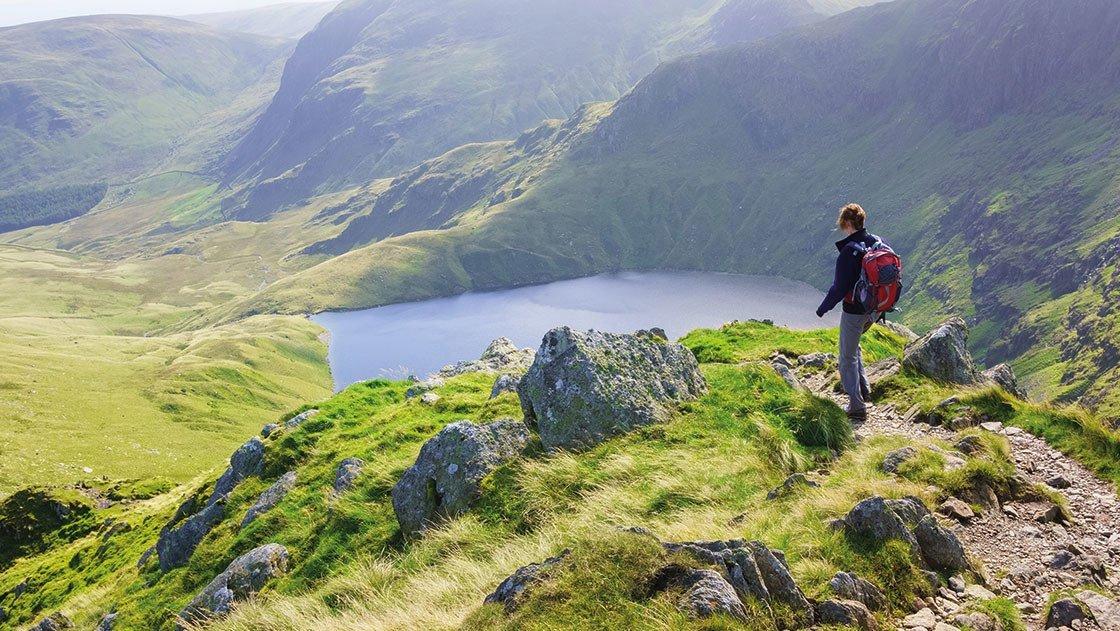 Ein Wanderer blickt hinab auf einen See