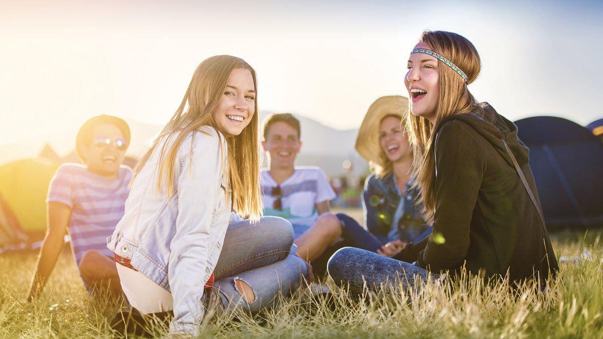 Jugendliche sitzen auf einer Wiese