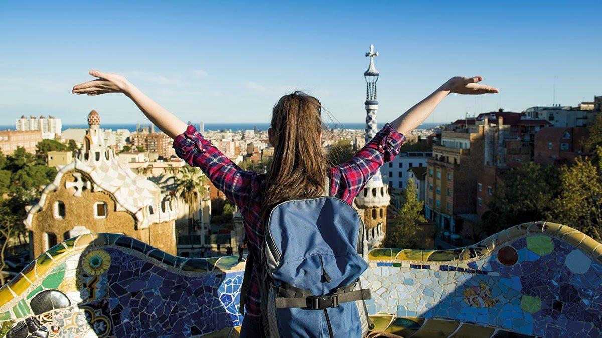 Junges Mädel breitet die Arme aus und freut sich am Anblick Barcelonas