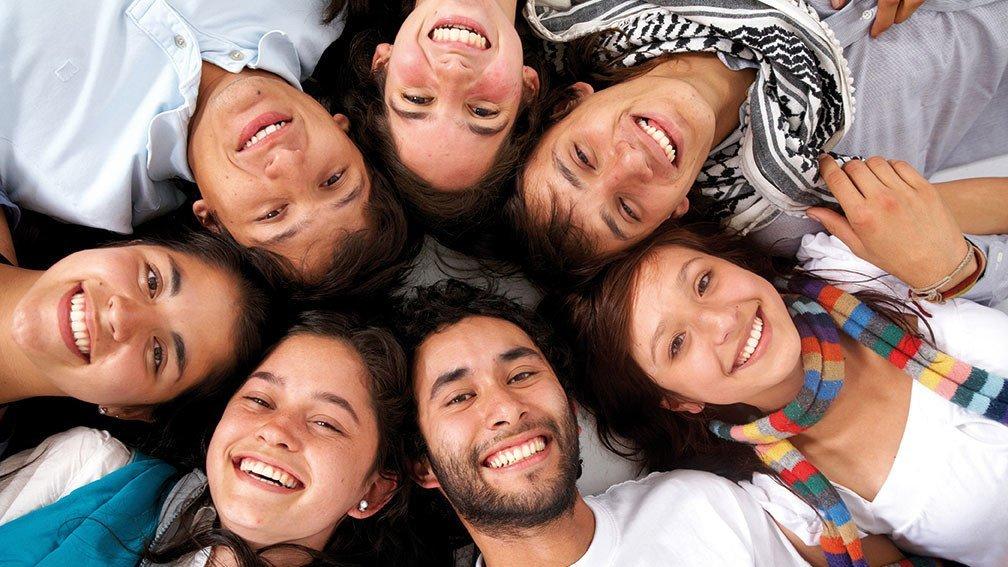 Viele Jugendliche liegen in einem Kreis