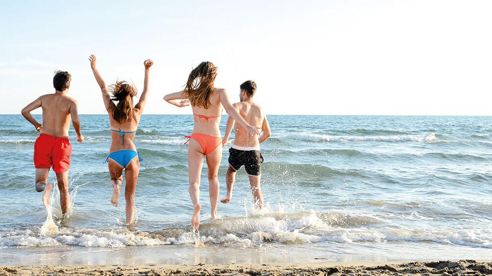 Jugendliche rennen ins Meer