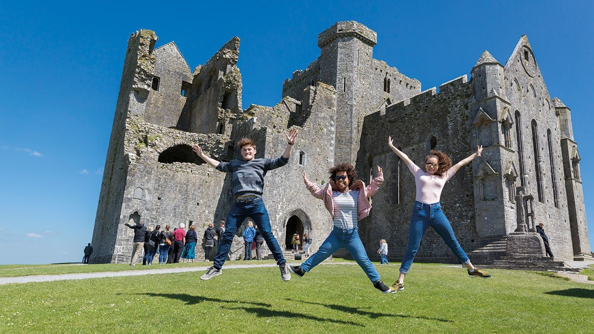 Drei Kinder jumpen vor dem Rock of Cashel