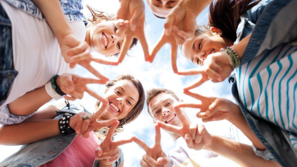 Gruppen von Jugendlichen halten ihre Finger zu einem Stern